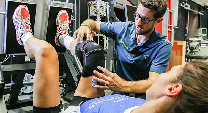 Ein Sportphysiotherapeut behandelt eine Sportlerin.