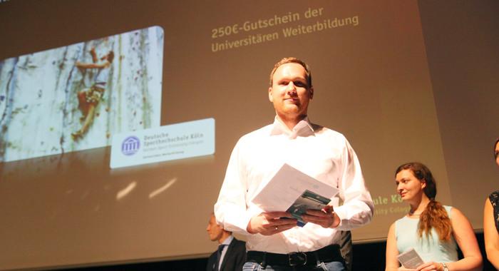 Dr. Sebastian Schwab mit einem Gutschein der Universitären Weiterbildung auf dem Absolventenball der Sporthochschule 2015