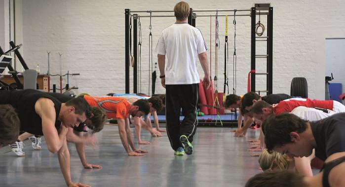 Trainer geht in Mitten von Trainierenden