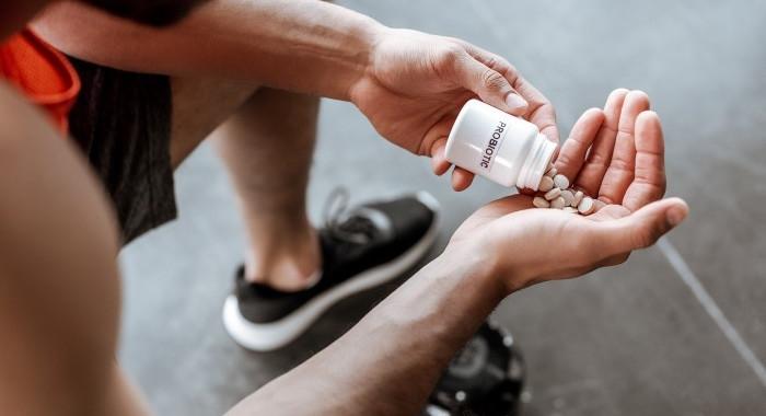 Junger Mann sitzt und schüttet sich Tabletten in die Hand