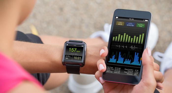 Eine Frau schaut sich mittels einer App und Handy ihre sportlichen Leistungsdaten an.