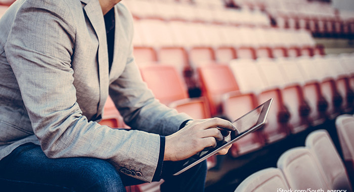 Sportmanager sitzt mit Tablet auf Tribüne ©iStock.com-South_agency