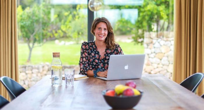 Lena Kadlec sitzt mit Laptop an einem Holztisch und schaut in die Kamera