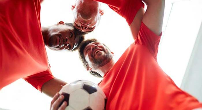 Drei Personen mit einem Fußball