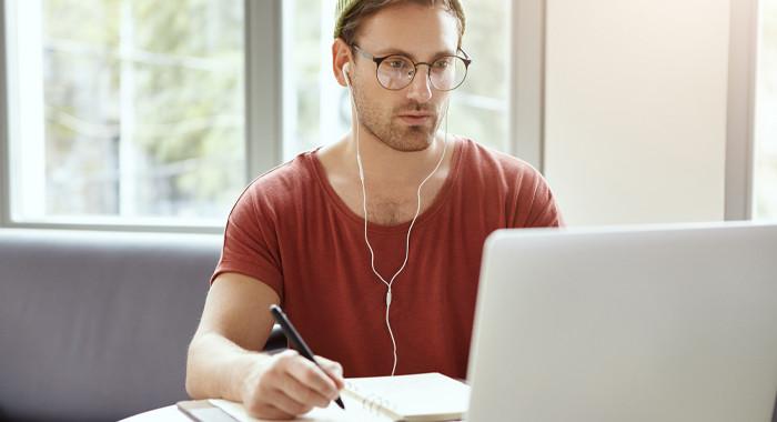 Ein Mann mit Brille schaut auf seinen Laptop.