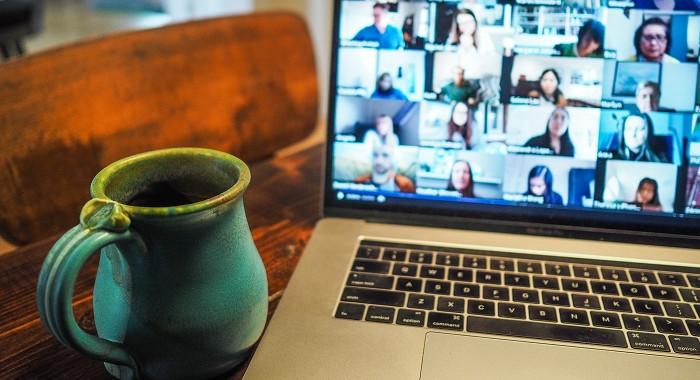 Auf einem Laptop sind zahlreiche Gesichter in einer Videokonferenz zu sehen.