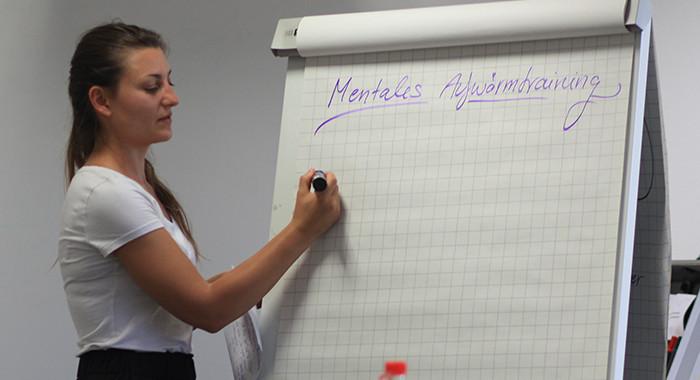 Eine Frau schreibt auf ein Plakat mit der Überschrift