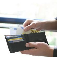 Geldscheine werden aus einem Portemonnaie genommen