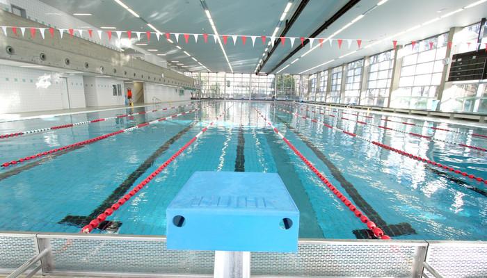 Blick über einen Startblock auf die 50m-Schwimmbahn.