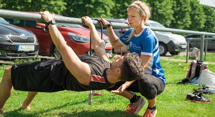 Personal Trainerin Jasmin Brandt hilft einem Teilnehmer bei der Haltung während einer Athletik-Übung.