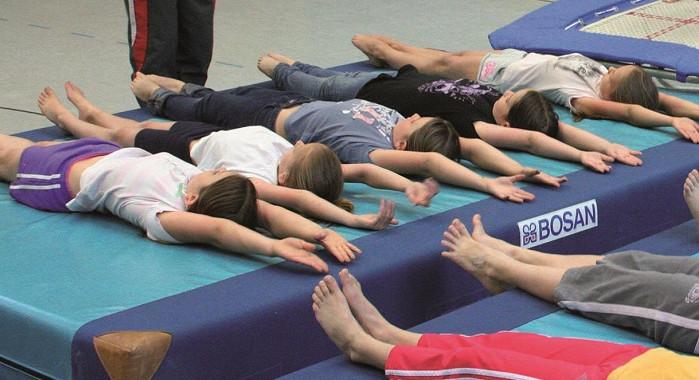Kinder liegen auf einer Sportmatte