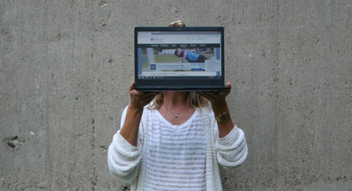 Eine Frau hält sich einen geöffneten Laptop vor das Gesicht.