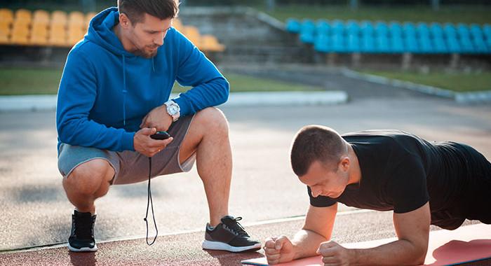 Ein Mann ist in Planking-Position, während sein Trainer ihn beaufsichtigt.