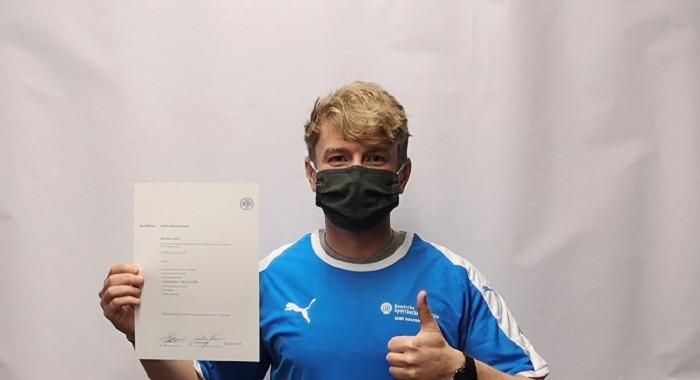 Damien Lewis zeigt sein erworbenes Zertifikat im DSHS Athletiktrainer